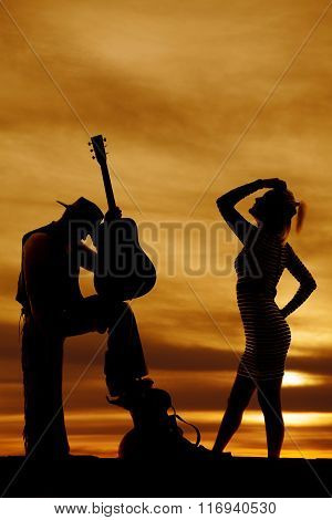Silhouette Of A Blond Woman Stand To Side Hand On Head And Cowboy Guitar