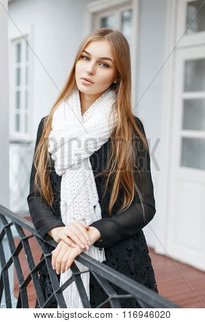 Beautiful Girl In A White Knitted Scarf And A Black Fashionable Dress Standing On The Veranda Of Hou