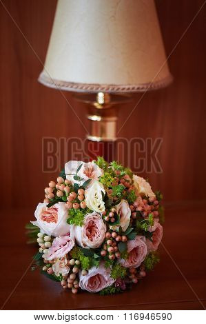 Delicate bride's bouquet of roses next to the lamp