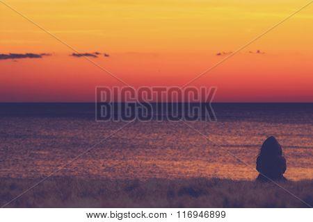 Girl watching the ocean horizon.