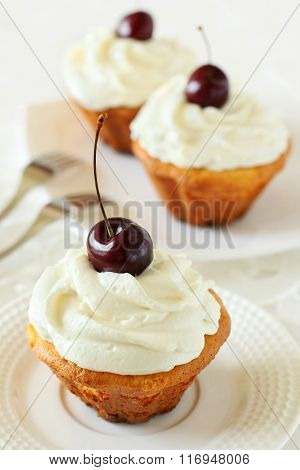 Three Cupcakes With Whipped Cream And Cherry