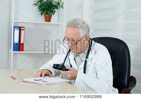 Mature Doctor With Loupe Study A  Literature