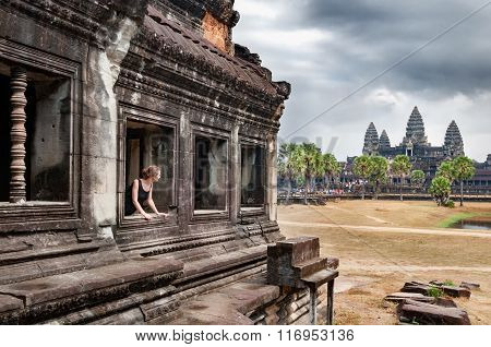 Girl looking at Angkor Wat temple in Cambodia