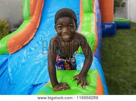 Smiling little boy sliding down an inflatable bounce house