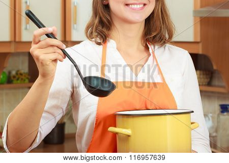 Woman With Ladle And Pot In Kitchen