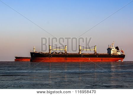 large tanker in the queue for loading of oil in icy sea