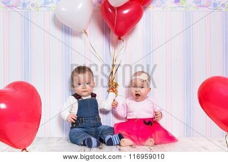 Baby boy and girl playing with heart balloons for valentines day.