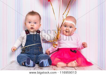 Baby boy and girl playing with hearts. Valentines day.