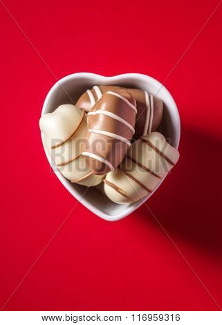 Gourmet date chocolates in a small heart shape bowl on bright red background, View from above.