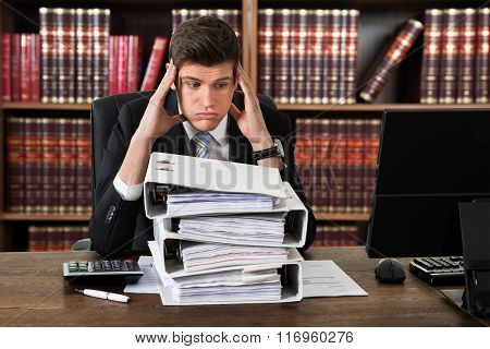 Stressed Attorney Looking At Heap Of Binders