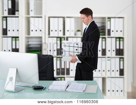 Businessman Carrying Binders By Desk