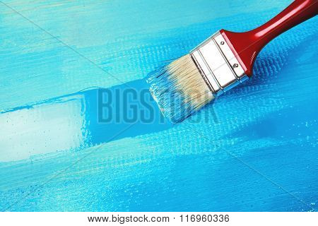 Varnishing a wooden shelf using paintbrush
