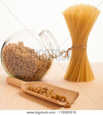 Wheat Spaghetti Standing Tied In Bundle And Glass Jar Filled With Spelt Pasta In The Shape Of Fusill
