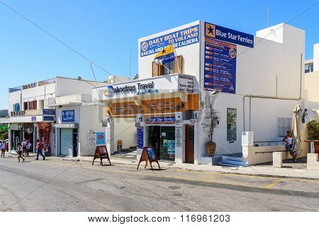 Main street of Thira town with office of Travel agency and tourists near it in Thira town at Santori