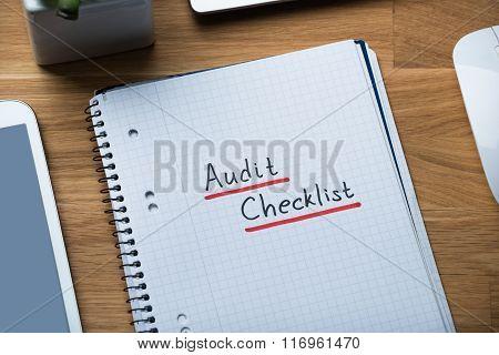 Audit Checklist Written On Notepad At Office Desk
