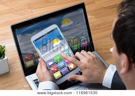 Businessman Using Smartphone And Laptop At Desk