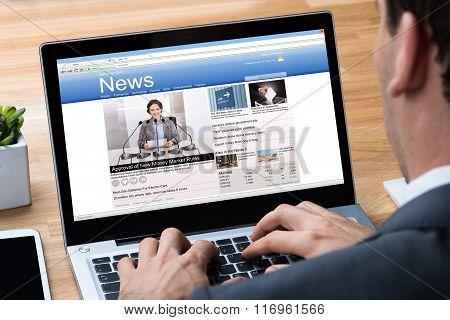 Businessman Reading News On Laptop At Desk