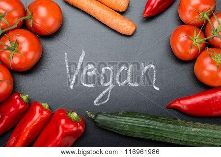 Vegan Written Amidst Fresh Vegetables On Blackboard