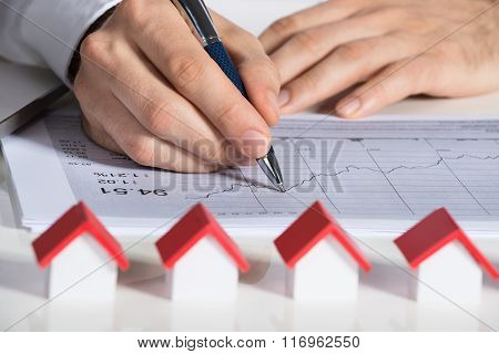 Businessman Preparing Financial Chart With House Models At Desk