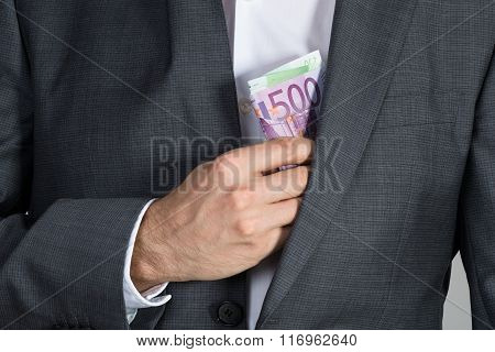 Businessman Putting Bribe In Suit Pocket