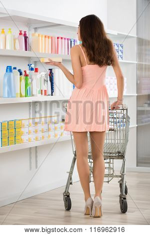 Woman With Shopping Cart Buying Beauty Products In Supermarket