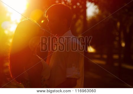 Young Couple Silhouette Hugging And Looking At Each Other Outdoors On The Sunset