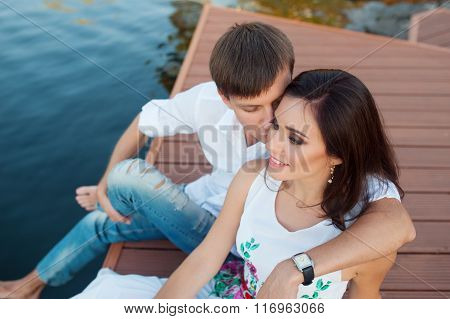 Man Embraces Girl Sitting On A Pier At The River Bank