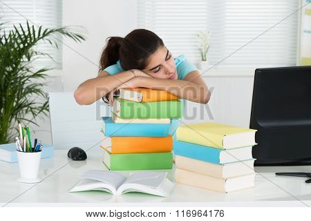 Student Resting On Stacked Books At Table