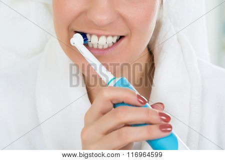 Woman In Bathrobe Brushing Teeth With Electric Toothbrush