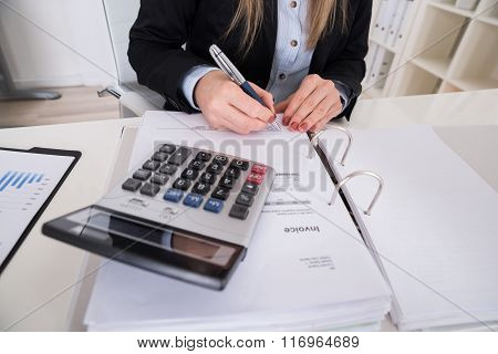 Businesswoman Calculating Invoice With Calculator