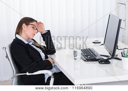 Businesswoman Having Headache In Office