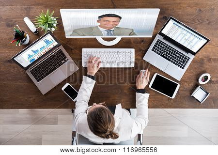 Businesswoman Videoconferencing With Senior Colleague