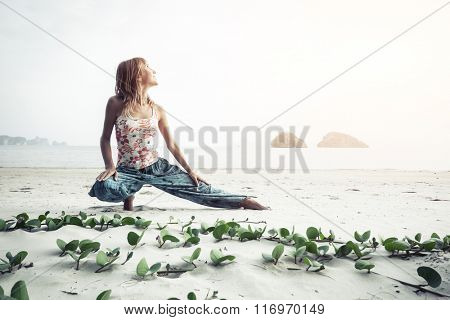 Lady stretching on the sandy beach