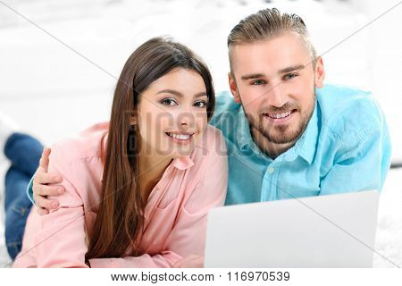 Happy couple lying on the floor and working on laptop