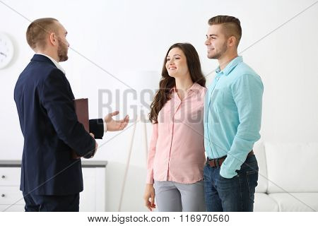 Happy family with estate agent, on light background