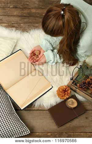 Woman holding nuts near book and basket of evergreen