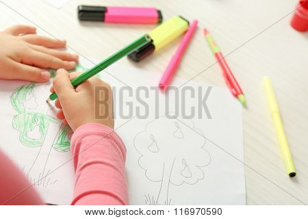Child drawing tree with pencils on paper, closeup
