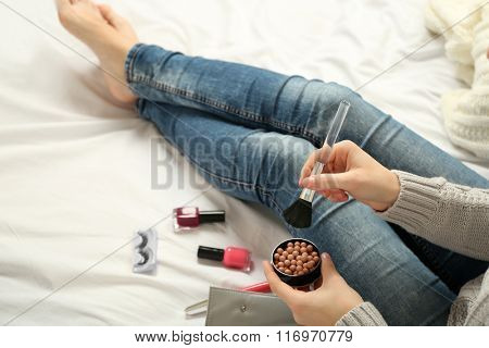 Woman applying makeup on her bed