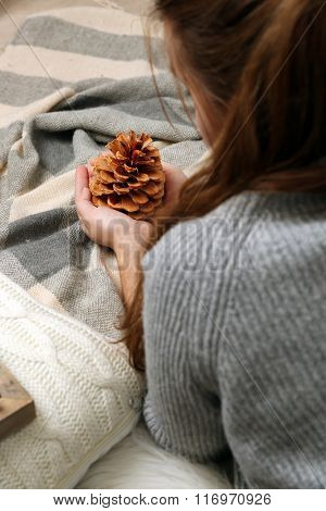 Woman holding pine cone, closeup