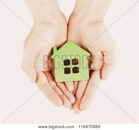 Female hands with model of house on light background