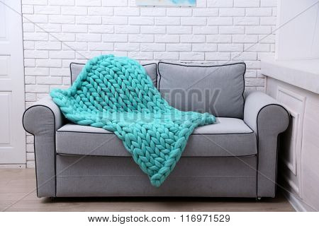 Knitted woolen blanket on sofa, on home interior background