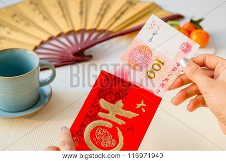 Woman's Hand Taking Out One Hundred Yuan From A Red Envelope.