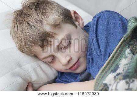 Little boy sleeping on sofa in room