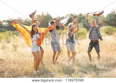 Carefree friends with guitars have fun, outdoors