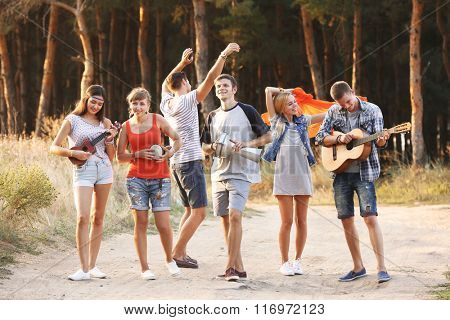 Happy smiling friends playing musical instruments in the forest outdoors