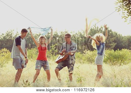 Joyful smiling friends dancing in the forest outdoors