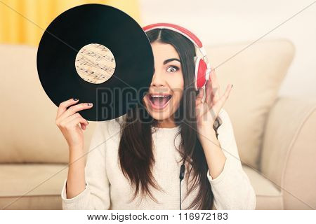 Happy young woman with headphones and vinyl record listening to music at home