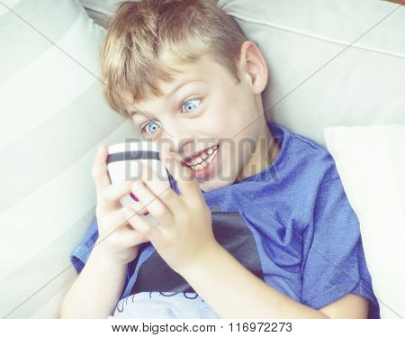 blonde boy playing phone at home