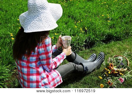 Young woman with cup of coffee sitting on meadow outdoors