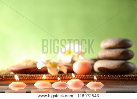 Spa still life with stones, candles and flowers in water on green blurred background